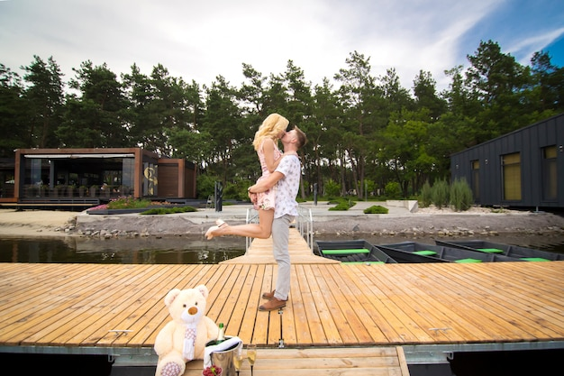 Loving young couple kisses on a wooden pier. lovestory on the pier