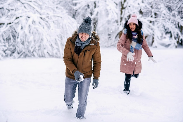 Loving young couple playing with snowballs in a winter park