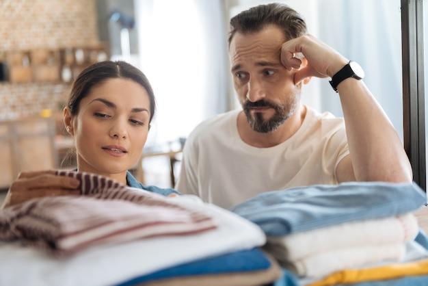 髭を生やした夫が手に寄りかかって妻を見つめながら服の近くでポーズをとる愛情のある若いカップル