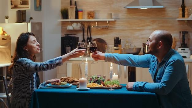 사랑하는 젊은 부부는 집에서 부엌에서 낭만적인 저녁 식사를 즐기면서 레드 와인 잔을 들고 건배를 합니다. 행복한 사람들이 식사를 하고, 식당에서 기념일을 축하하고, 낭만적인 토스트