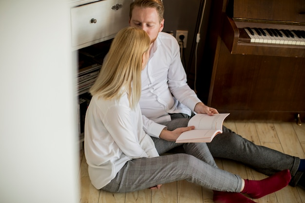 Loving young couple reading a book in the room