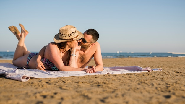 Loving young couple relaxing together and lying on sand at summer beach