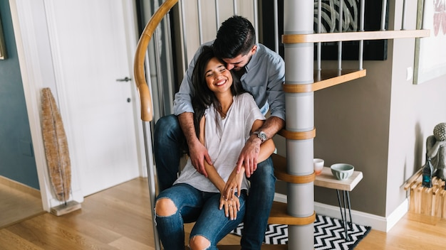 Loving young couple sitting on spiral staircase
