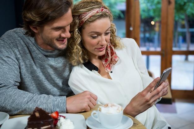 食堂のテーブルでスマートフォンを使用して若いカップルを愛する