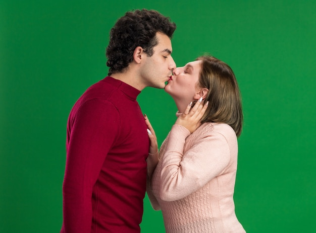Loving young couple on valentine's day standing in profile view kissing woman touching hair keeping hand on man's chest isolated on green wall