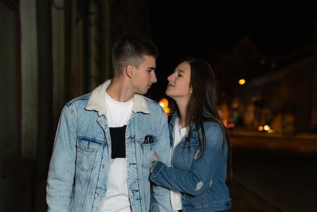 通りを歩いている愛情のある若いカップル。夜のロマンチックなデートの若いカップル。背景の夜の街。