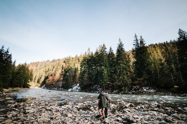 愛する若いカップルは自然の中を歩きます。石のある川が森の間を山に流れています。風景。