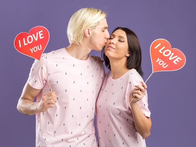 Loving young couple wearing pajamas holding i love you photo booth props with closed eyes woman putting hand on man's shoulder and man kissing her on cheek isolated on purple wall