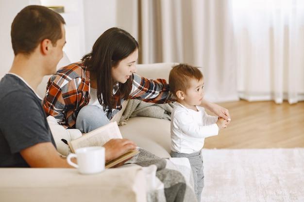 愛する若い家族はリラックスして、幼い息子が一緒に遊んで週末の時間を楽しんでいます