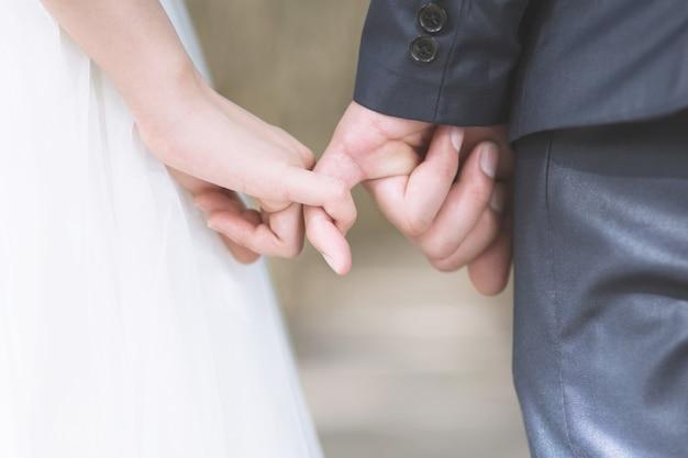 Любящая молодая влюбленная супружеская пара, держась за руки и стоя вместе в сцене свадьбы в день свадьбы