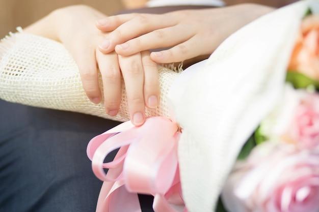 愛する若い愛の夫婦が手をつないで一緒に立つ