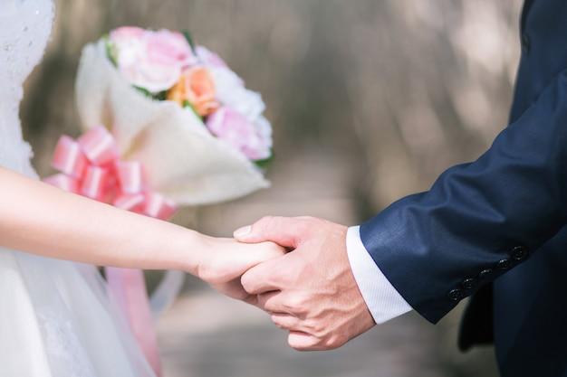 Любящая молодая любовь супружеская пара, держась за руки и стоять вместе