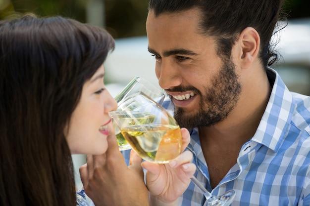 Любящий молодой мужчина и женщина пьют вино в парке