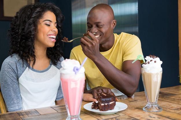 コーヒーショップで女性にデザートを与える愛情のある若い男