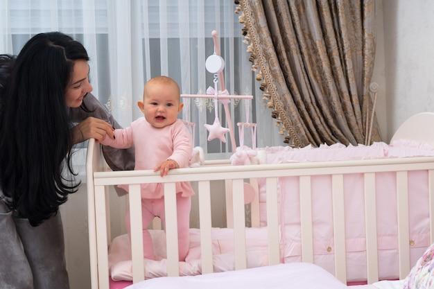 彼女の笑顔の小さな娘が保育園で彼女のベッドの中に立つのを手伝う愛情のある若い母親