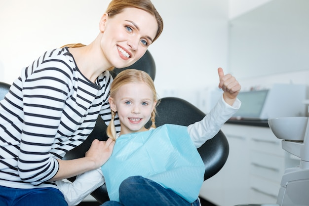 Любящая молодая мать обнимает свою маленькую дочь и позирует вместе с ней, пока девушка сидит в кресле стоматолога и ждет осмотра