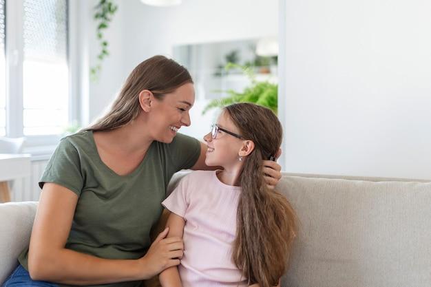 家で一緒に時間を楽しんでいる笑顔のかわいい面白い子供の娘を抱きしめて笑っている愛情のある若い母親、遊んで楽しんでいる小さな子供の女の子と幸せな家族のシングルママは抱きしめたり抱きしめたりする喜びを感じます