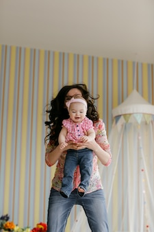 自宅で一緒に時間を楽しんでいるかわいい面白い子供の娘の笑顔を抱きしめ笑って愛する若い母親