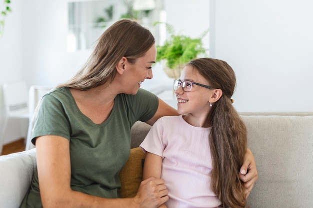 Loving young mother laughing embracing smiling cute funny kid daughter enjoying time together at home, happy family single mom with little child girl having fun playing feel joy cuddling and hugging