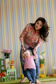 Loving young mother laughing embracing smiling cute funny kid daughter enjoying time together at home