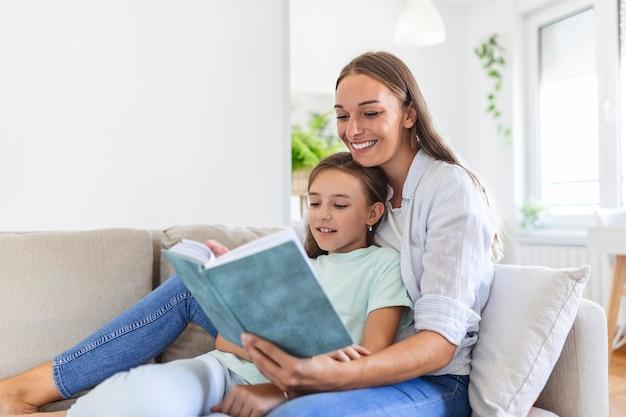 사랑스러운 어린 엄마가 사랑스러운 어린 딸에게 책을 읽어주고, 거실의 아늑한 소파에 앉아, 엄마가 미취학 아동을 가르치고, 가족이 함께 집에서 주말을 보내고, 어린이 교육