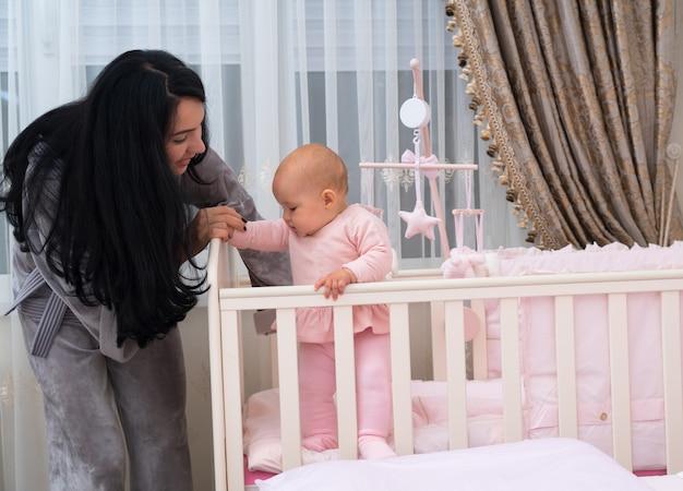 愛らしい若い母親が、愛らしい小さな赤ん坊の娘に、保育園のベビーベッドの隅でバランスをとるのを手伝って立つように教えています