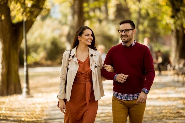Любящая молодая женщина и мужчина гуляют в городском парке, держась за руки