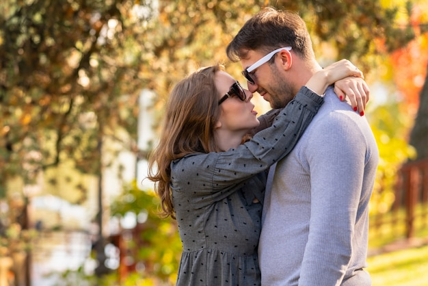Loving young woman hugging her husband rubbing noses and looking into his eyes in a close up portrait in an autumn park