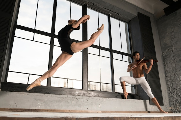 Low angle of ballerina and musician