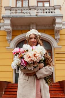 Basso angolo di bella donna che tiene il mazzo di fiori