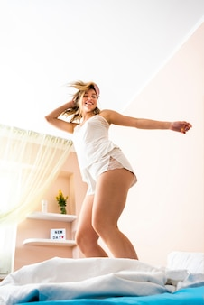 Low angle beautiful woman jumping in bed