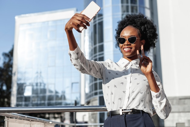 Low angle beautiful woman taking selfies