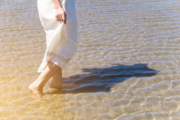 Низкий угол за женщиной, идущей босиком по пляжу