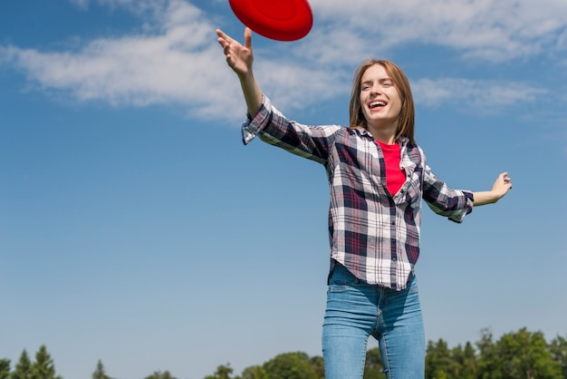 Low angle blonde girl playing with a red frisbee