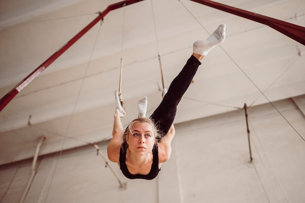 体操リングのローアングル金髪女性トレーニング