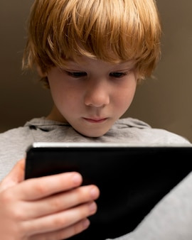 Low angle of boy sitting in char and using tablet