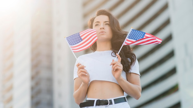 Low angle brunette woman holding usa flags