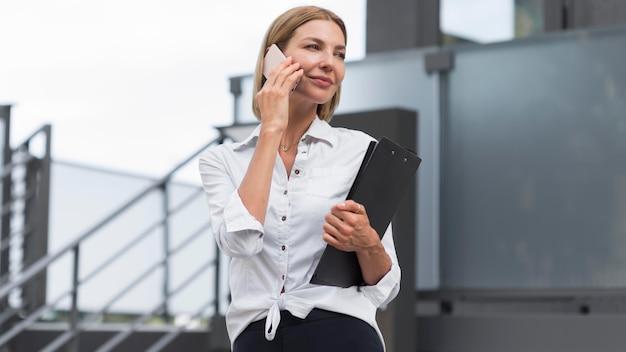 電話で話している低角度のビジネス女性