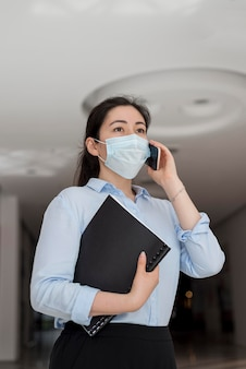 Low angle business woman wearing mask