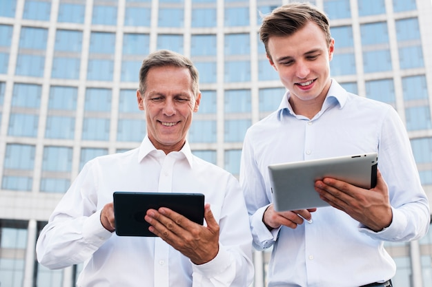 Low angle businessmen looking at tablets