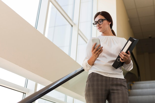 Low angle of businesswoman holding binder and working on smartphone