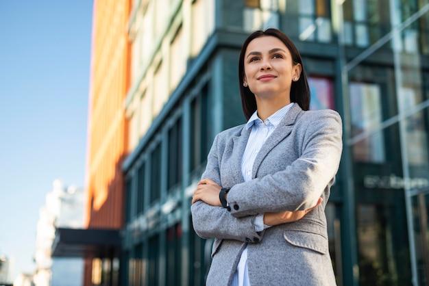 Basso angolo di imprenditrice in posa con le braccia incrociate all'aperto