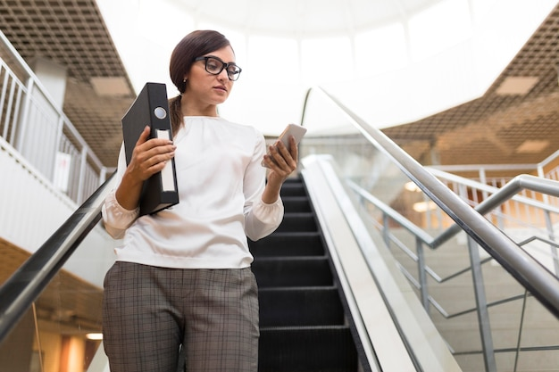 Low angle of businesswoman with smartphone and binder on escalator