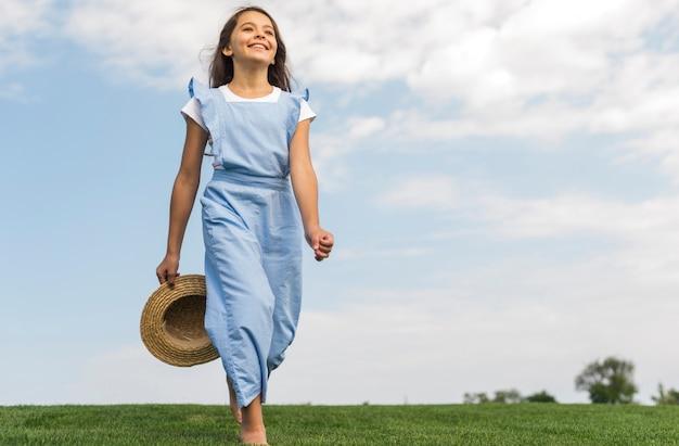 Low angle cheerful girl walking barefoot on grass