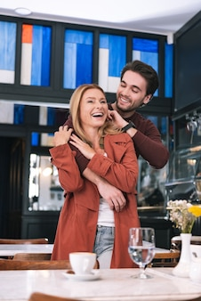 Low angle of cheerful jovial couple hugging and making laugh