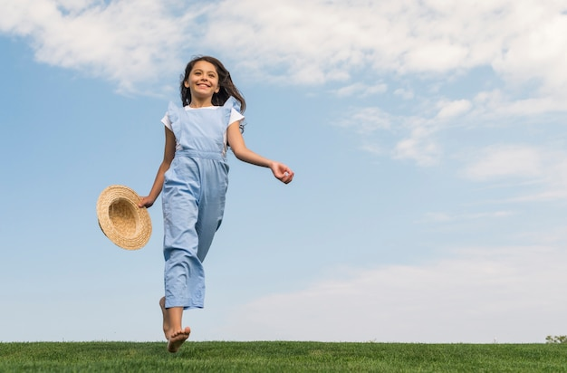Low angle cheerful little girl running on grass