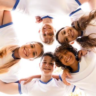 Bambini ad angolo basso in abbigliamento sportivo guardando verso il basso