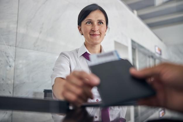 탑승권과 여권이 있는 남성의 손을 낮은 각도로 닫고 비행 전에 아름다운 세관 직원에게 제공합니다.
