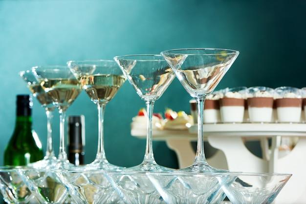 낮은 각도 레스토랑 식탁 유리 알코올 축제 축하 음료 음료 분위기에서 파티 테이블에 마티니 안경의 총을 닫습니다.
