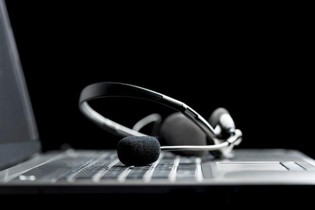 コールセンターを介したハンズフリー通信、クライアントサービス、または企業サポートの概念である、開いているラップトップコンピューターのキーボードにあるヘッドセットの低角度のクローズアップビュー